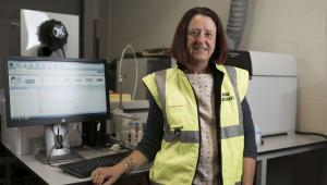 Professor Kym Jarvis standing in yellow high-viz jacket in front of IT equipment