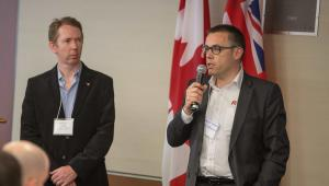 Roger Estrada, CEO of R53 Engineering, using a microphone to address an event during the GBIP visit to Canada. Looking on (left) is Gordon Jolly, ‎Industrial Technology Advisor - ‎National Research Council Canada. UK and Canadian flags on the wall behind.