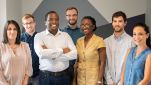 Founders Neciah and Josephine Dorh surrounded by three male and three females members of the FluoretIQ team posing against a grey diagrammatic office background..