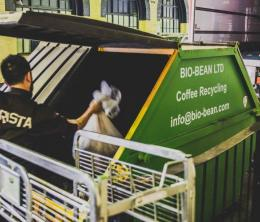 Man lifting a bag of coffee grounds into a recycling skip in a warehouse.