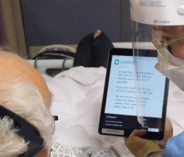 View from behind elderly patient's head of a nurse in full personal protection holding up a tablet with text explaining how oxygen treatment might make him feel.