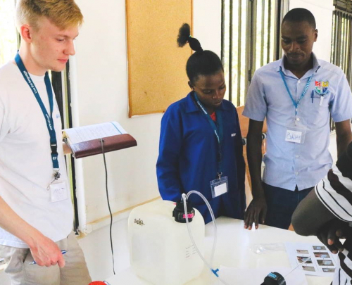 Tom Stakes, Blue Tap founder and Chief Technical Officer, holding a notepad and looking at a chlorine doser being tested in Uganda, watched by three members of the local water treatment project team, one female and two male.