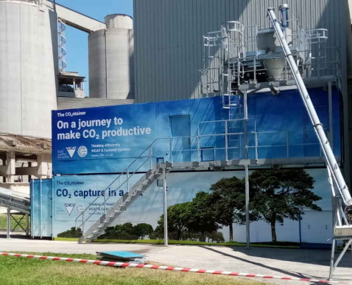 Picture of a cement plant in France with carbon capture and use facility emblazoned with blue banner artwork promoting clean tech ambitions