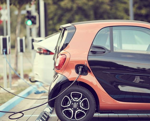 Orange and black Smart car being recharged at street side.