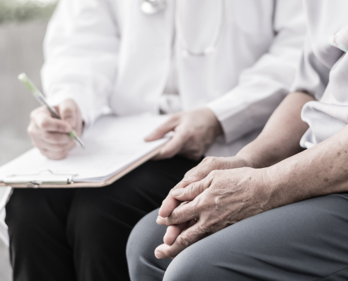 Close-up of elderly patient's hands clasped resting on his legs, with clinician in the background taking notes on a clipboard.