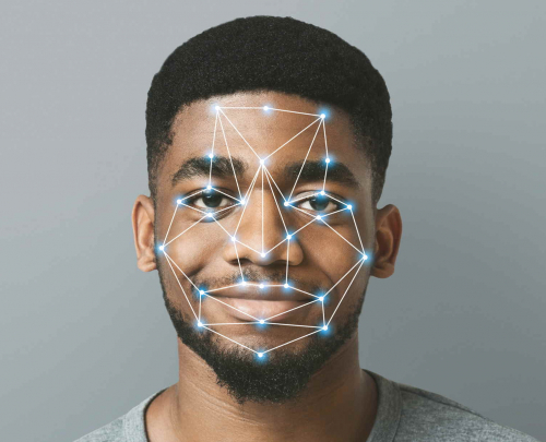 Young male, smiling, with cgi data points overlaid on face.