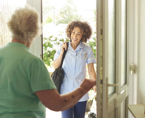 Elderly woman in light green top, with back to the camera, opening the door to community nurse, carrying black shoulder bag, arriving on a social care visit
