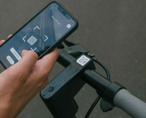 A man's hand on a mobile displaying an app fixed to handlebars of an electric scooter.