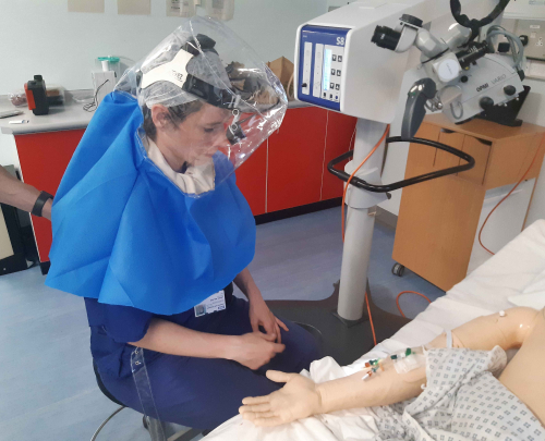 A female doctor wearing the Air-Hood standing next to a dummy patient during a demonstration of the technology at Lewisham and Greenwich NHS Trust.